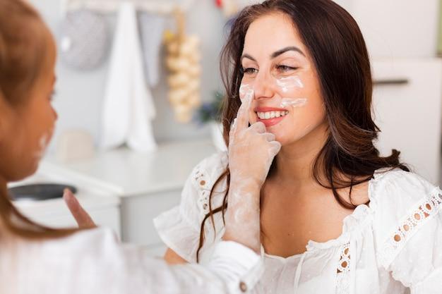 Niña pintando con harina su cara de madre