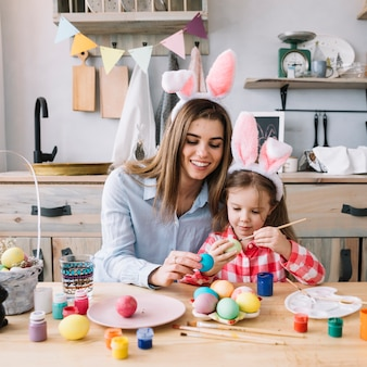 Niña pintando huevos para pascua con madre