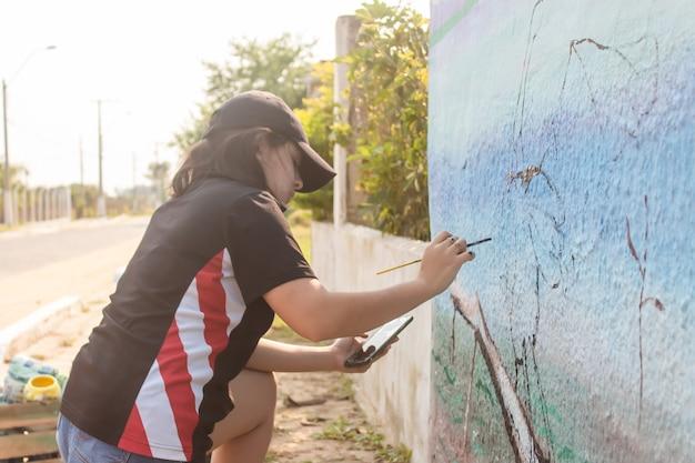 Niña pintando una pared de la calle con su teléfono celular como referencia.