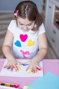 Niña pintando con sus manos y dedos en casa