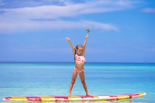 Niña con piruleta divertirse en tabla de surf en el mar