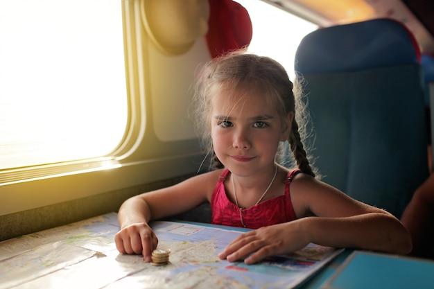 Niña con la planificación de sus vacaciones económicas durante el viaje en tren