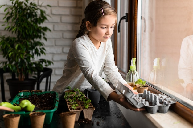 Niña plantar semillas junto a la ventana