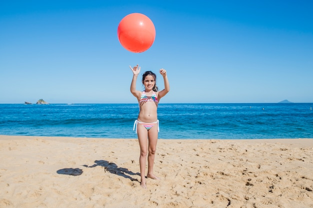 Niña, playa y pelota