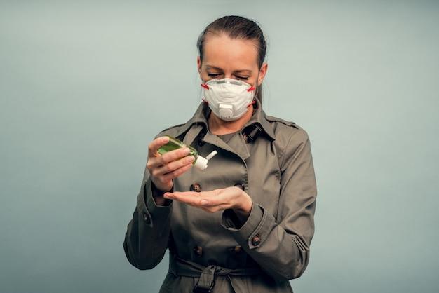 Una niña se pone una máscara protectora. uso de un gel antiséptico. protección respiratoria del coronavirus. equipo de protección personal para una pandemia de infección viral. covid-19.