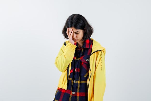 Niña poniendo la mano en la cara con camisa a cuadros y chaqueta amarilla y mirando cansado, vista frontal.