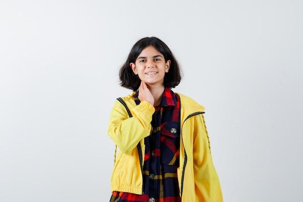 Niña poniendo la mano en el cuello con camisa a cuadros y chaqueta amarilla y mirando feliz. vista frontal.