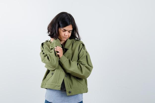 Niña poniendo la mano en el cuello, con dolor de cabeza en suéter gris, chaqueta caqui, pantalón de mezclilla y mirando exhausto, vista frontal.