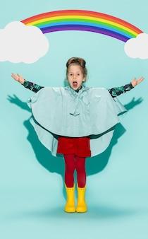 Niña posando en estilo de moda con ropa de otoño sobre fondo azul. botas de goma amarillas.
