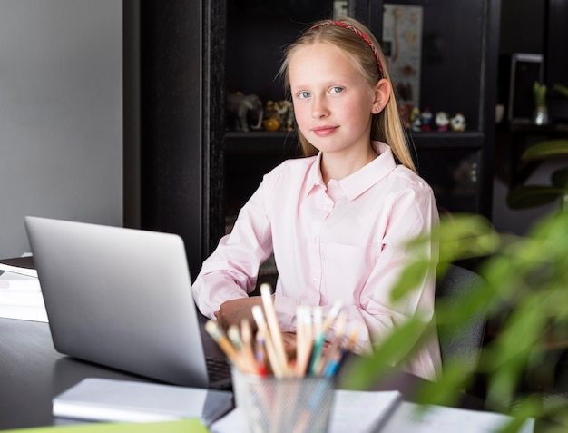 Niña posando junto a su computadora portátil