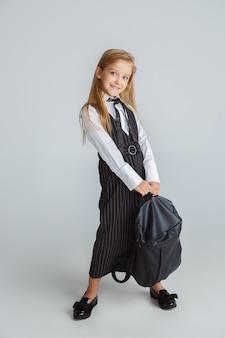 Niña posando en uniforme escolar con mochila en pared blanca