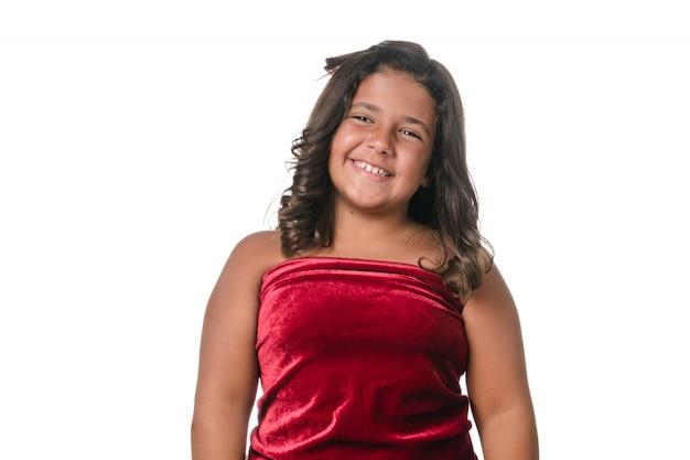 Niña posando con vestido de terciopelo rojo sobre fondo blanco.