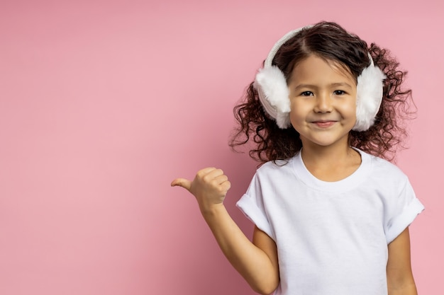 Niña positiva con cabello rizado, vestida con camiseta blanca, orejeras peludas, apuntando a un lado con el pulgar con expresión alegre