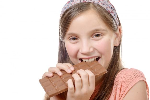 Niña preadolescente come chocolate, aislado en blanco