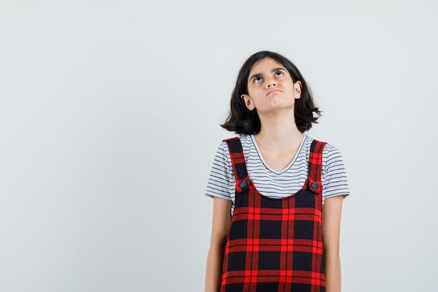 Niña preadolescente mirando hacia arriba en camiseta