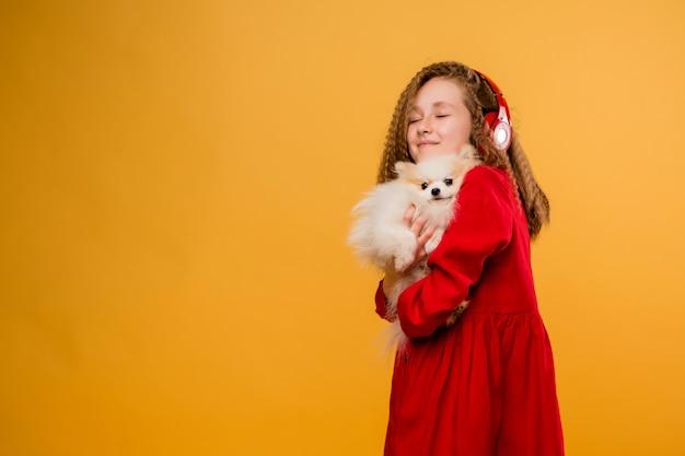 Niña preadolescente con un perro pequeño en sus manos