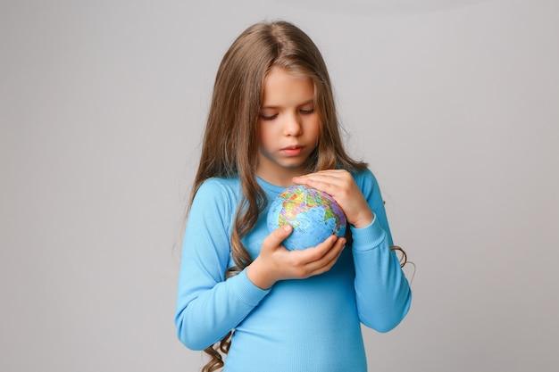 Niña preadolescente sosteniendo un globo terráqueo