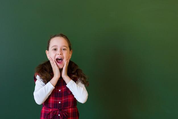 Niña preescolar colegiala feliz en vestido a cuadros de pie en clase cerca de una pizarra verde.