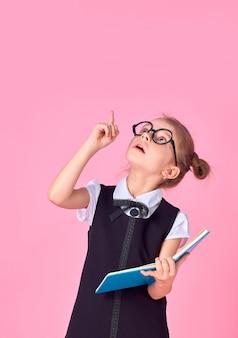 Niña preescolar con gafas sosteniendo un libro, levantó la mano y el dedo hacia arriba
