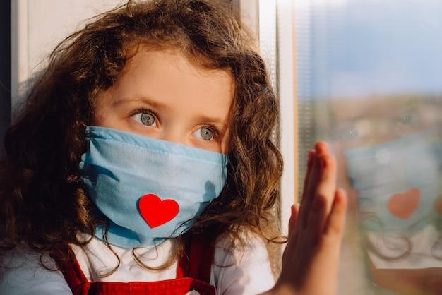 Niña preescolar en mascarilla médica estéril con corazón rojo, sentado en el alféizar de la ventana en casa, de la mano sobre el vidrio, mirando fuera de la ventana borrosa. quedarse en casa y el concepto de cuarentena