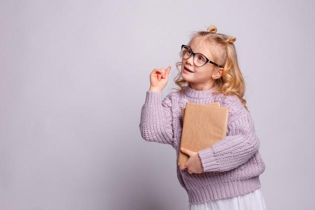 Una niña preescolar rubia con gafas sosteniendo un libro, levantó su dedo sobre un fondo gris