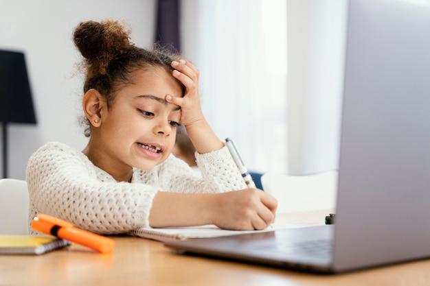 Niña preocupada en casa durante la escuela en línea con portátil