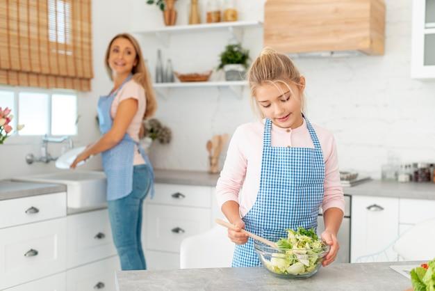 Niña preparando ensalada supervisada por su madre