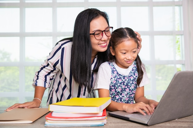 Niña de primaria estudiando computador con maestra