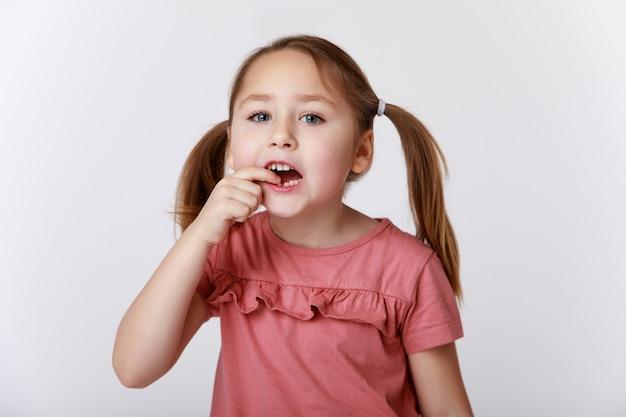 Niña con el primer diente de leche oscilante