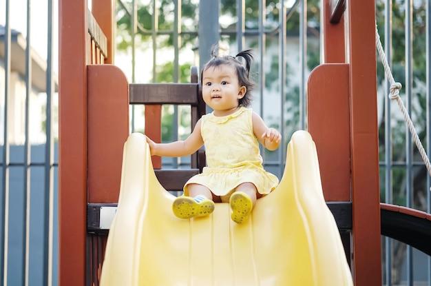 La niña del primer juega un resbalador en el fondo del patio