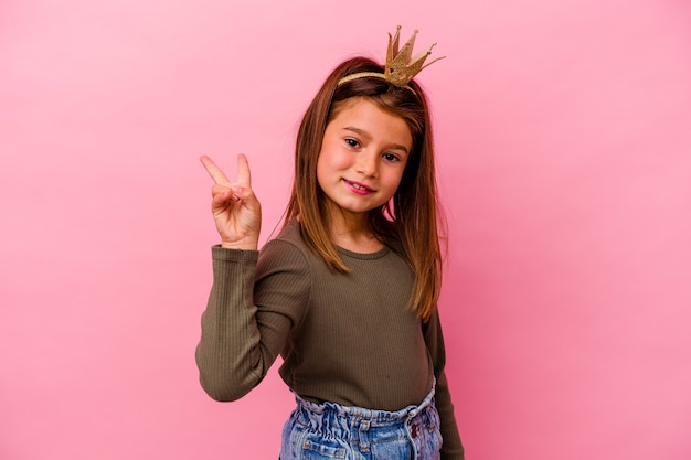 Niña princesa con corona aislada sobre fondo rosa alegre y despreocupado mostrando un símbolo de paz con los dedos.