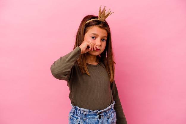 Niña princesa con corona aislada sobre fondo rosa con los dedos en los labios guardando un secreto.