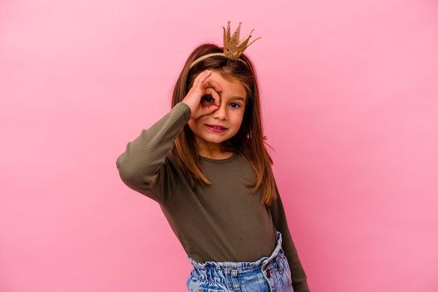 Niña princesa con corona aislada sobre fondo rosa emocionado manteniendo el gesto ok en el ojo.