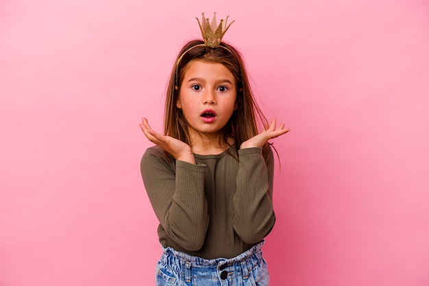 Niña princesa con corona aislada sobre fondo rosa sorprendida y conmocionada.