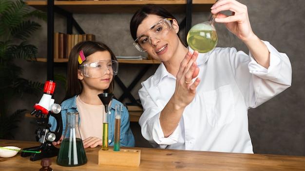 Niña y profesor haciendo experimentos científicos con microscopio.