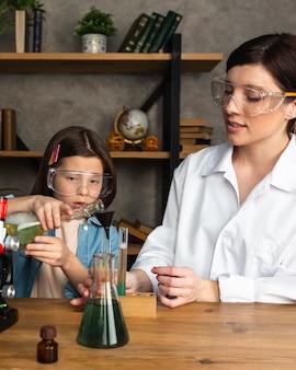 Niña y profesor haciendo experimentos científicos con tubos de ensayo.