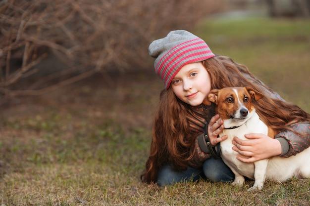 Niña que abraza a su amigo un perro adentro al aire libre. amistad, protección animal, concepto de estilo de vida.
