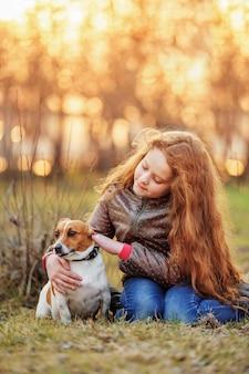 Niña que abraza a su amigo un perro adentro al aire libre.