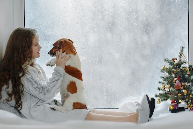 Niña que abraza su perro de perrito, sentándose en ventana y esperando la navidad.