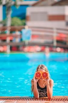Niña que cubre los ojos con mitades naranjas cerca de los ojos en la piscina de fondo