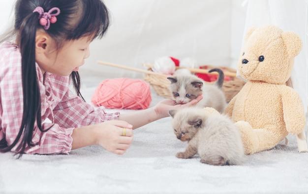 Niña que juega con el gato en casa, concepto de la nave del amigo.