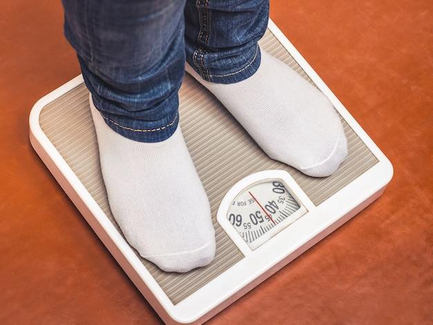 Una niña que lleva un estilo de vida saludable, se para en la balanza y mide su peso