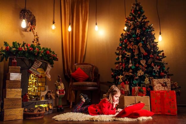 Niña que miente en alfombra con los regalos alrededor usando la tableta en la almohada roja.