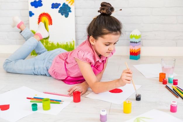 Niña que miente en la pintura del suelo con color de agua con el cepillo de pintura en el papel