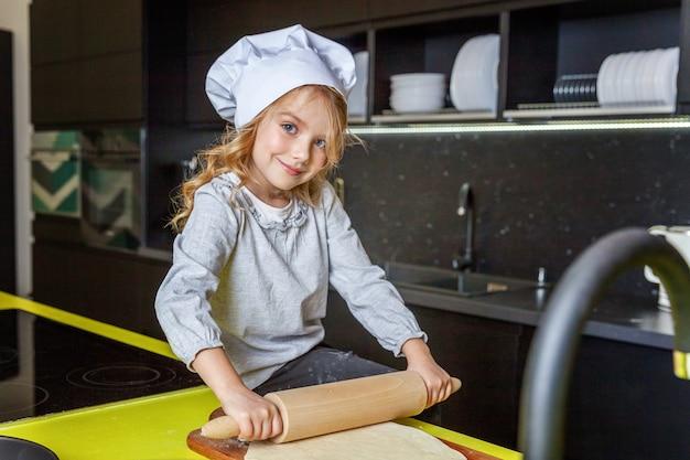 La niña que prepara la pasta, cuece la empanada de manzana hecha en casa del día de fiesta en cocina