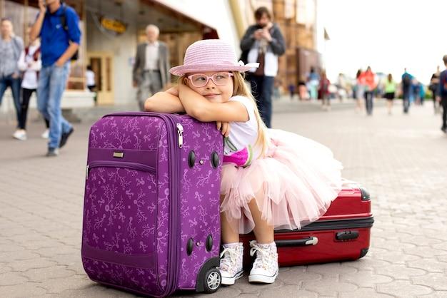 Niña que se sienta en una maleta en la estación de tren.