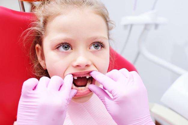 Niña que se sienta en silla dental en la oficina pediátrica de los dentistas.