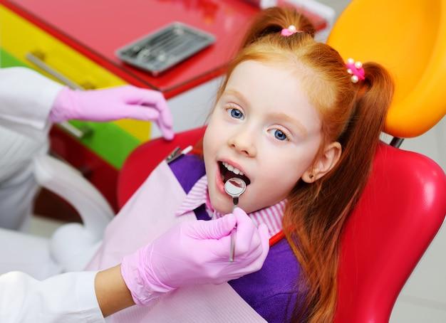 Niña que sonríe en silla dental roja. el dentista examina los dientes del paciente del niño.