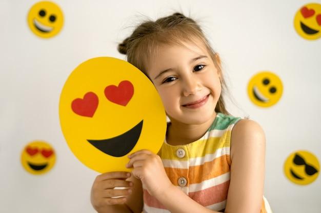 Una niña que sonríe con todos sus dientes tiene un emoji de amor en sus manos