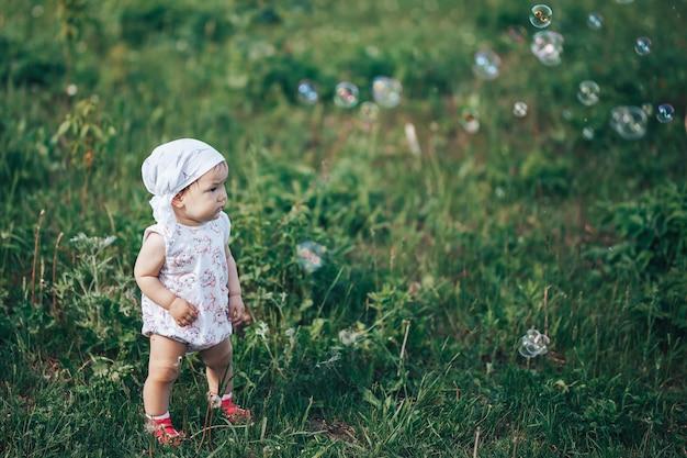 Una niña que sopla pompas de jabón, retrato de primavera hermoso niño de un año